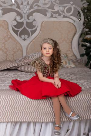 Niña hermosa en un vestido de noche rojo del árbol de Navidad. Chica de rojo en las decoraciones de Navidad. Niño lindo en la cama