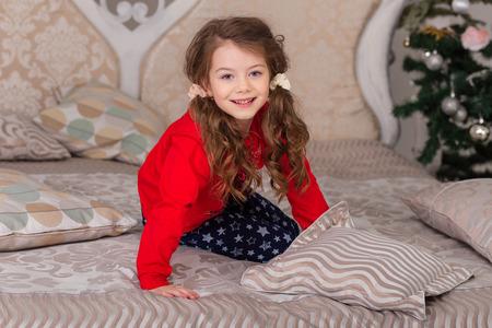 Süßes Mädchen im Pyjama für Bett fertig. Das Kind schwelgt im Bett vor dem Einschlafen