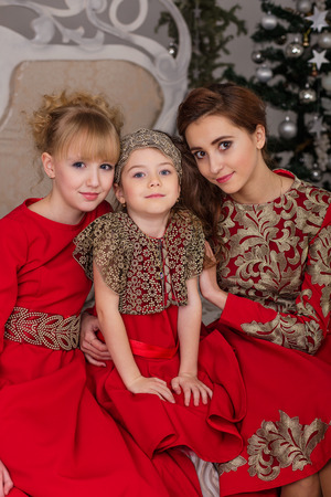 anticipation: Three girls in a red evening dress the Christmas tree. Beautiful girlfriend in the anticipation of Christmas. Stock Photo