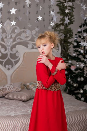 threshold: Portrait of a young beautiful blonde in a red dress at the Christmas tree. Lovely girl on the threshold of Christmas Stock Photo