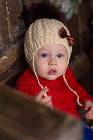 Portrait ittle girl in a knitted red sweater and fur hat. Cute baby in christmas decorations