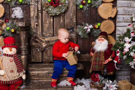 Portrait little girl in a knitted red sweater. Cute baby sitting in christmas decorations.The child opens a gift Stock Photo
