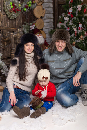 Young couple with child in fur hats sitting in a Christmas tree. Family in a hat and knitted things