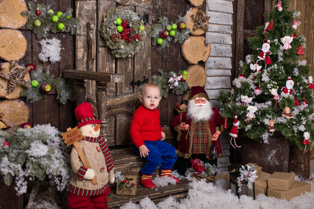 Portrait little girl in a knitted red sweater. Cute baby sitting in christmas decorations