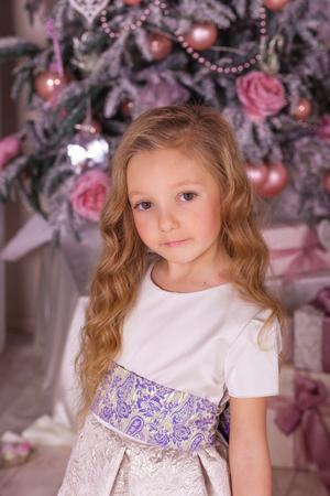 guirnaldas de navidad: Dulce niña de hermosas decoraciones de Navidad. La niña en traje de noche en el árbol de Navidad. Foto de archivo