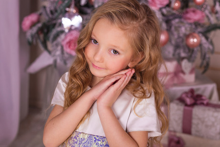 guirnaldas de navidad: Sweet girl in beautiful Christmas decorations. The little girl in evening dress at the Christmas tree.