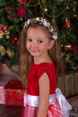 pine wreaths: Little beautiful girl in red dress at the Christmas tree. Portrait of cute baby in the New Year decorations