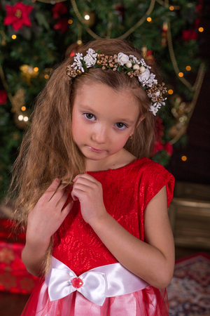 guirnaldas de navidad: Little beautiful girl in red dress at the Christmas tree. Portrait of cute baby in the New Year decorations
