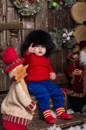 ittle: Portrait ittle girl in a knitted red sweater and fur hat. Cute baby in christmas decorations