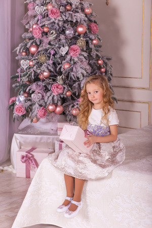 pine wreaths: Sweet girl in beautiful Christmas decorations. The little girl in evening dress at the Christmas tree.