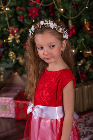 little beautiful girl in red dress at the christmas tree portrait of cute baby in