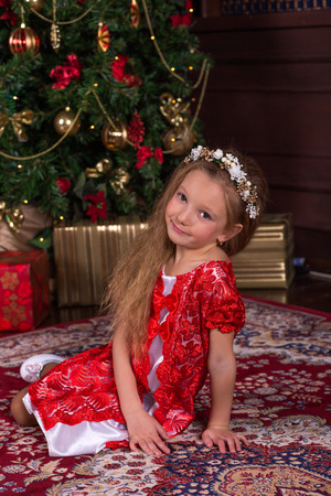 Little beautiful girl in red dress at the Christmas tree. Portrait of cute baby in the New Year decorations