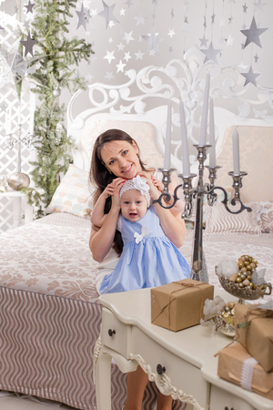 Portrait of mother and daughter in beautiful dresses in the christmas decoration Stock Photo