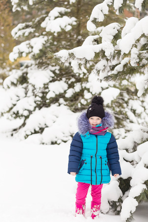 vibrance: Portrait of a Girl in the winter forest. A child playing in the snow