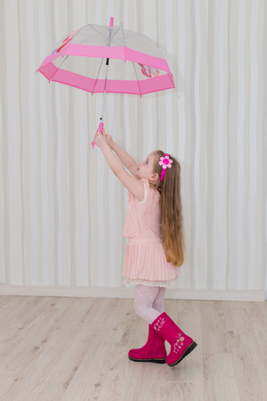 Sweet girl with a pink umbrella at home. The child is preparing for rain