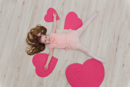 Sweet girl lying on the floor with decorations in the form of heart. Feast day of St. Valentine
