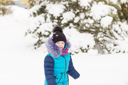 Portrait of a Girl in the winter forest. A child playing in the snow