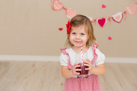 Little cute girl on the background wall of a house. The child in the scenery in the form of hearts. The kid drinks juice Stock Photo