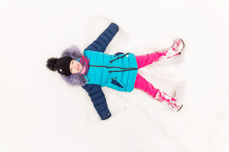 vibrance: Portrait of a girl in the winter forest. A child playing in the snow. The kid is lying in the snow on the ground