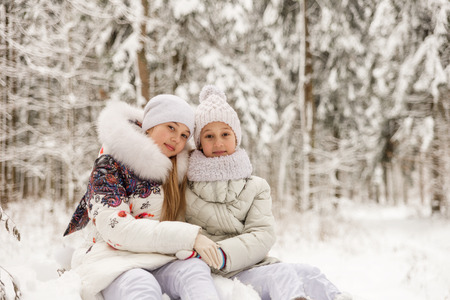 seson: Two girlfriends playing in a winter forest. The sisters have a rest in the open air in winter