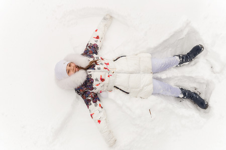 seson: Beautiful girl playing in a winter forest. The child have a rest in the open air in winter. The child lies on snow Stock Photo