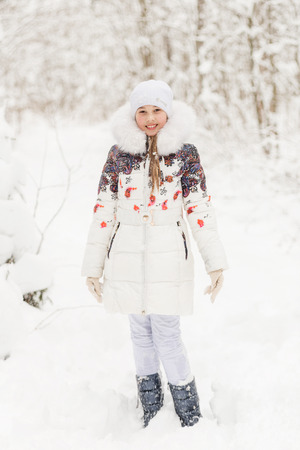 seson: Cute girl playing in a winter forest. The child have a rest in the open air in winter