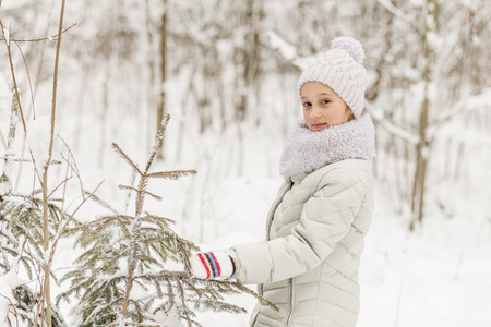 seson: Beautiful girl playing in a winter forest. The child have a rest in the open air in winter