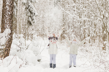 Two girlfriends playing in a winter forest. The sisters have a rest in the open air in winter