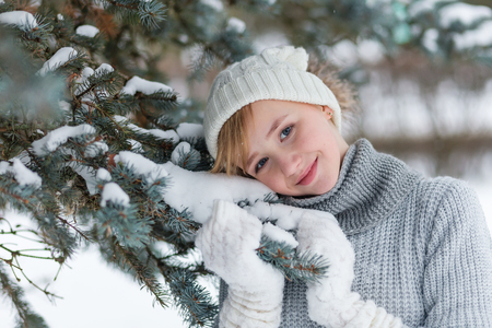 Beautiful girl in a white hat and mittens in the winter snowy forest. Cute child in a knitted dress near a tree in the winter