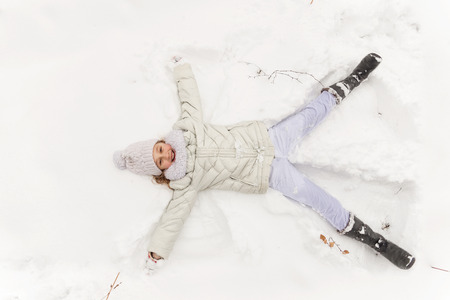 Beautiful girl playing in a winter forest. The child have a rest in the open air in winter. The child lies on snow Stock Photo