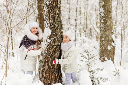 seson: Two girlfriends playing in a winter forest. The sisters have a rest in the open air in winter. Children playing hide and seek