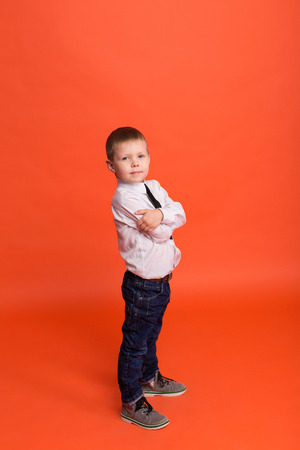 Little boy posing in the studio on a red background.