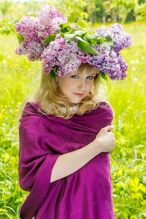 Young woman with flowers in green park. Young girl in beautiful wreath of lilac flowers Stock Photo