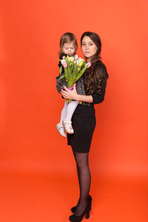 Beautiful sister with a bouquet of flowers on a red background in studio