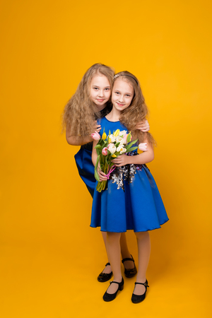 women's fashion: Two beautiful young girl with a bouquet of flowers on a yellow background in studio