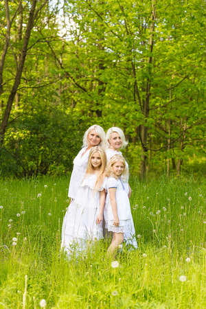 brightness: A large family is resting in nature. Mom and daughters play in the park in the summer. Blondes posing outdoors