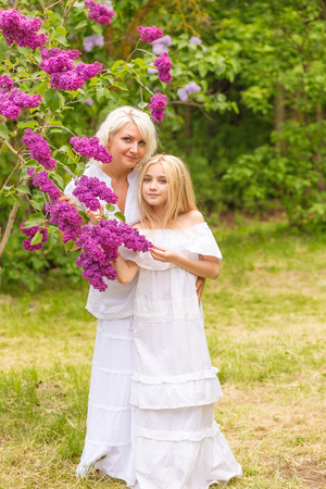 Portrait of a blonde in a lilac. Mom and daughter in flowers. Girls posing against a lilac background