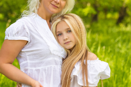 A large family is resting in nature. Mom and daughters play in the park in the summer. Blondes posing outdoors