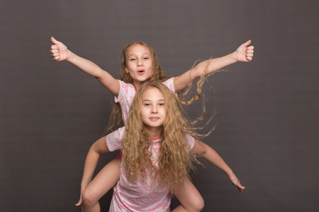 Beautiful two girls in pink pajamas play before going to bed. Sisters in pajamas are getting ready for bed. Fighting with pillows before bedtime