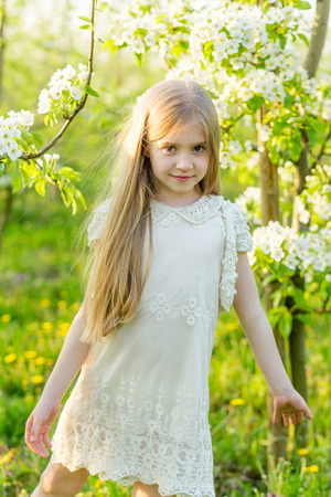 Portrait a beautiful little girl  a flowering garden in the spring. Cute child with blond hair in a blooming garden at sunset