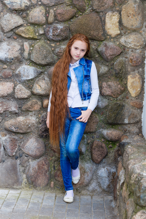rapunzel: Beautiful redhead girl with long hair up to knees posing outdoors