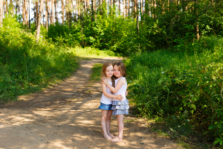 Two little girl girl friends hugging in the forest on a sunny afternoon Stock Photo