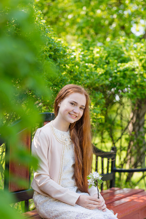 rapunzel: Portrait of a cute girl with long red hair in the park. Beautiful redhead girl in a blossoming summer garden Stock Photo