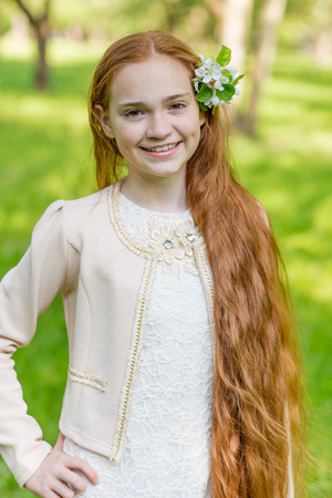 rapunzel: Portrait of a cute girl with long red hair in the park. Beautiful redhead girl in a blossoming summer garden. Redhead child with a flower in his hair