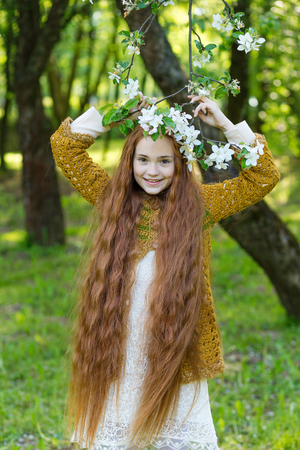 chic: Portrait of a cute girl with long red hair in the park. Beautiful redhead girl in a blossoming summer garden. Redhead child with a flower in his hair