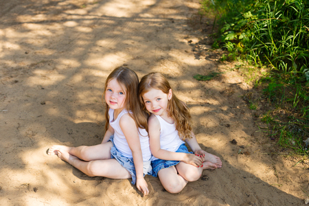 Dos amigos de la niña chica que abrazan en el bosque en una tarde soleada