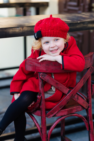 sympathetic: Portrait of a beautiful little girl with red hair in a red coat outdoors in spring. Redheded child in a red hat and coat Stock Photo