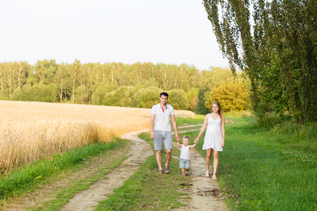 A young family with a small boy waiting for a second child. Future parents with a child outdoors in summer Stock Photo