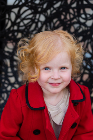 trait: Portrait of a beautiful little girl with red hair in a red coat outdoors in spring