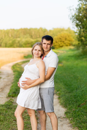 Portrait of beautiful young future parents outdoors in summer Stock Photo